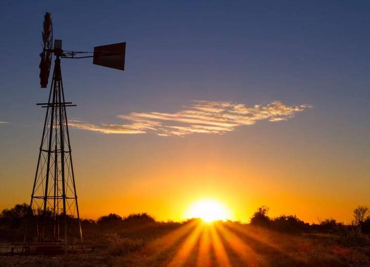 Outback setting with windmill in foreground.